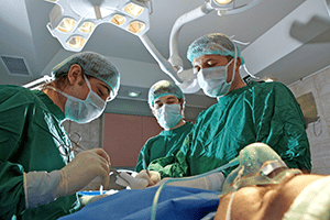 Three surgeons operating on patient in the OR